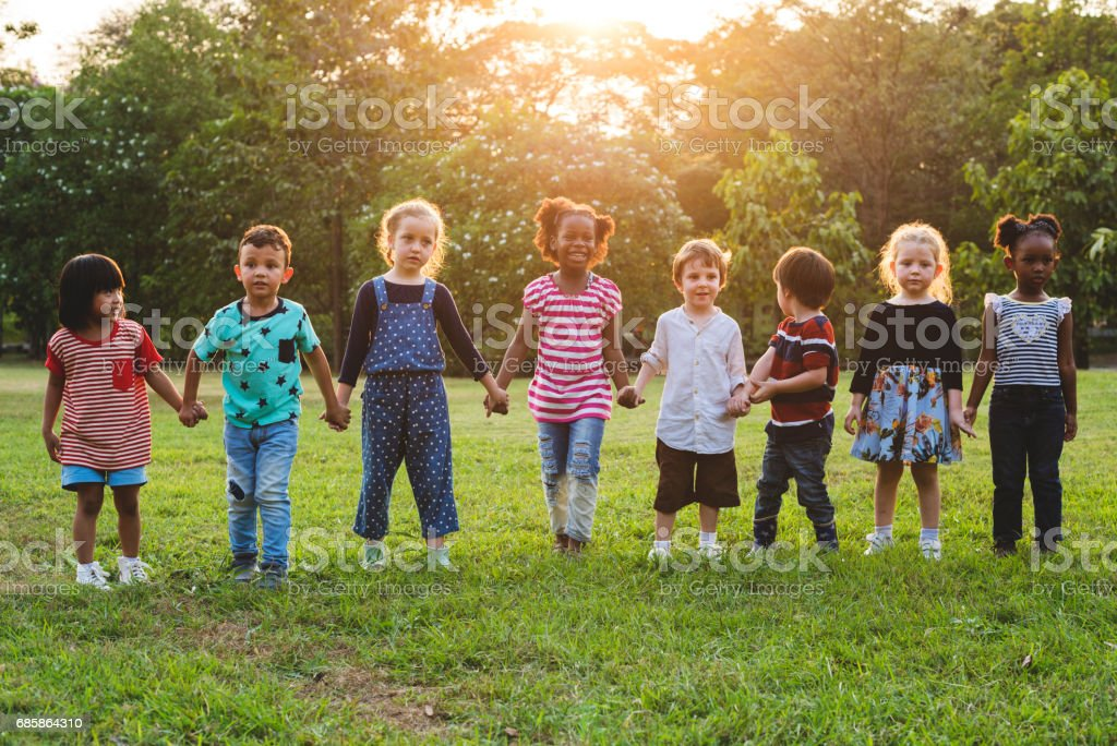 Kids standing in a row holding hands in a park stock photo