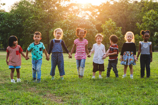 Kids standing in a row holding hands in a park - foto de stock