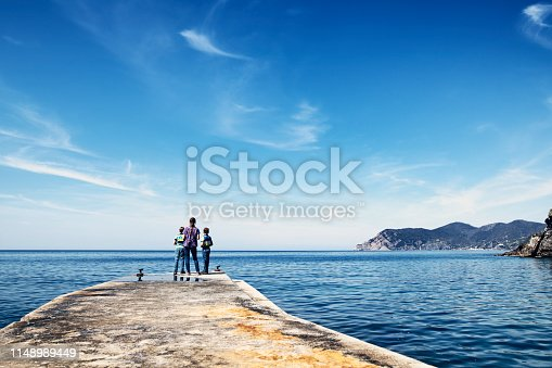 Family sightseeing Corniglia in Cinque Terre National Park - a UNESCO World Heritage Site. Three kids are standing on pier in the old harbour of Corniglia, Cinque Terre, Italy  Nikon D850