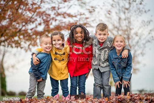 A multi-ethnic group of elementary age children are standing in a row outside at the park on a beautiful fall day. They have their arms around each other and are smiling and looking at the camera.