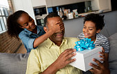 Happy African American kids surprising their father with a gift at home and covering his eyes - Father's Day concepts