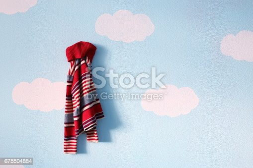 678651100 istock photo Kids sweater on the blue sky background 675504884
