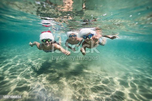 Little girl and her brother are having fun swimming underwater in sea during summer Christmas.  Kids are wearing Santa hats. Nikon D850