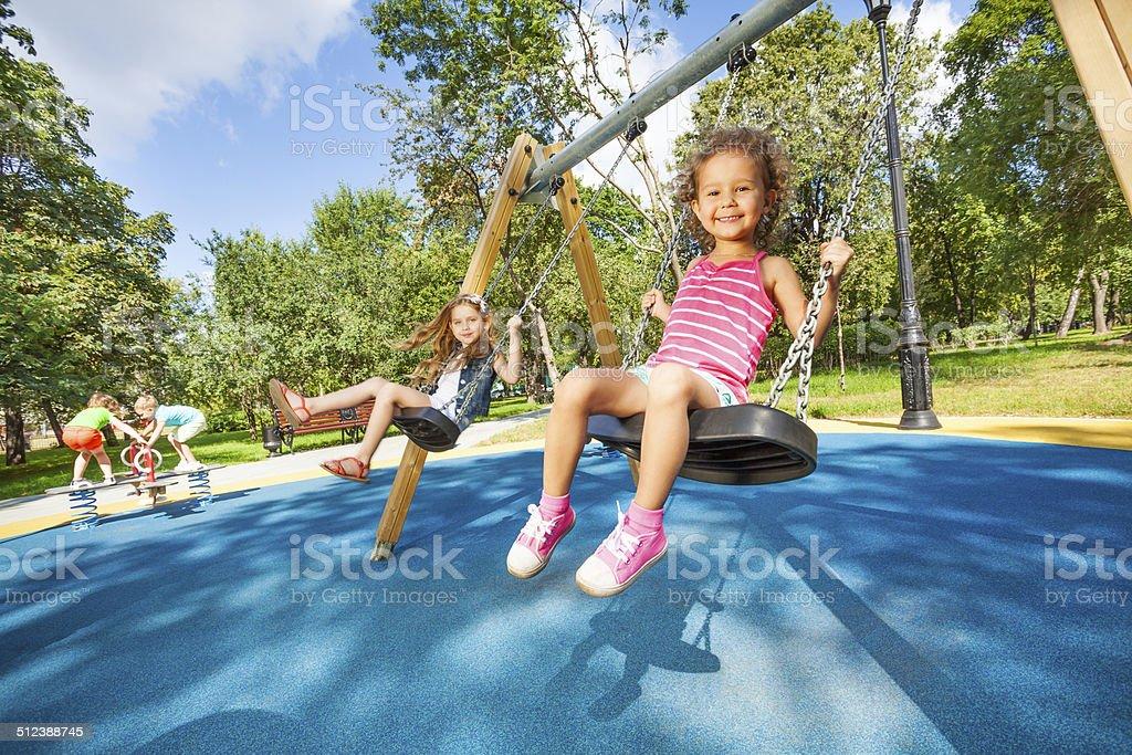 Kids swing on playground stock photo