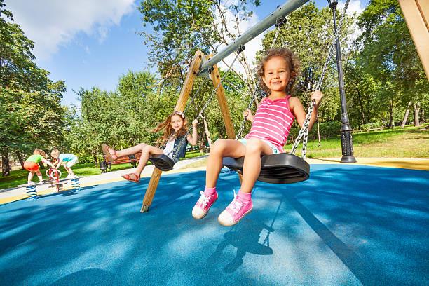 crianças balanço no parque infantil - balouço imagens e fotografias de stock
