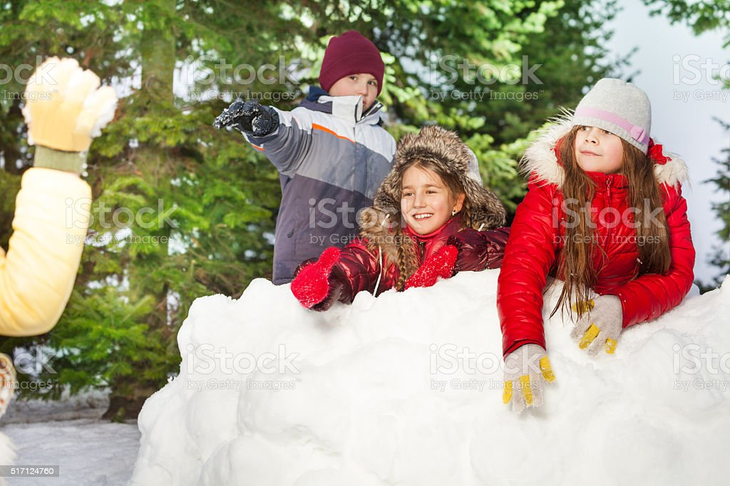 Kids throwing snowballs hiding after snow tower stock photo