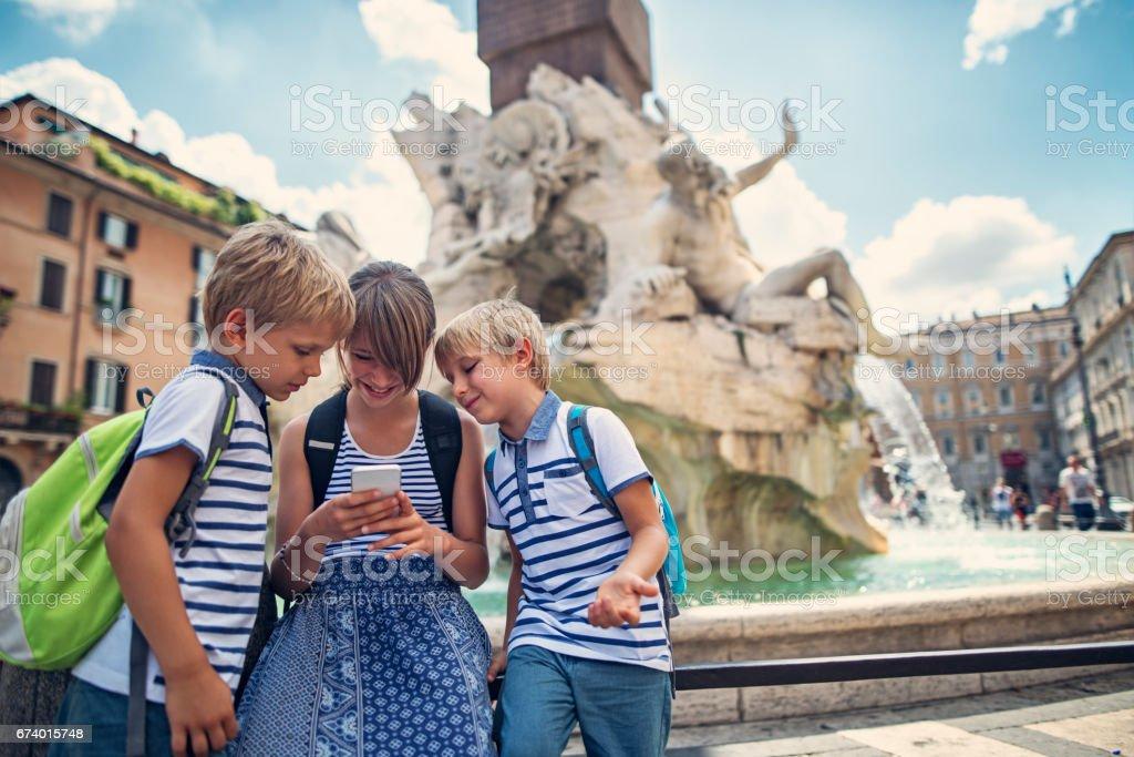Kids tourists sending photos at Fontana dei Fiumi, Rome stock photo
