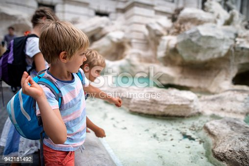 Kids sightseeing Rome, Italy. They are throwing coins into Trevi Fountain, Rome. Nikon D800