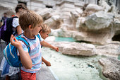 Kids sightseeing Rome, Italy. They are throwing coins into Trevi Fountain, Rome.\nNikon D800