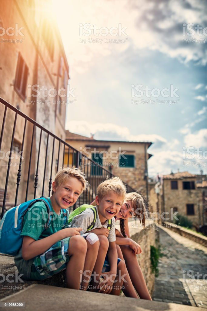 Kids tourists visiting beautiful italian town in Tuscany stock photo
