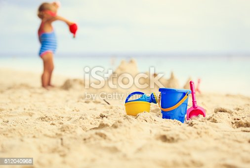 512726470 istock photo kids toys and little girl building sandcastle 512040968