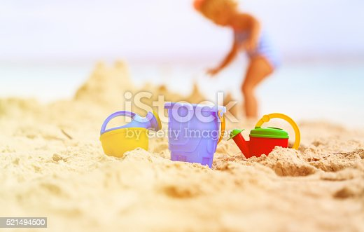 512726470 istock photo kids toys and little girl building sandcastle 521494500