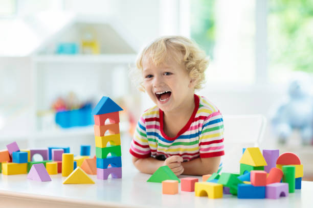 Kids toys. Child building tower of toy blocks. stock photo