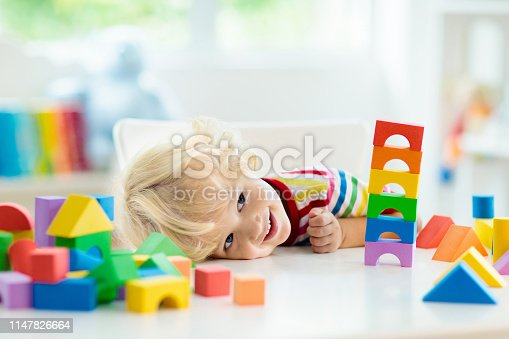 istock Kids toys. Child building tower of toy blocks. 1147826664