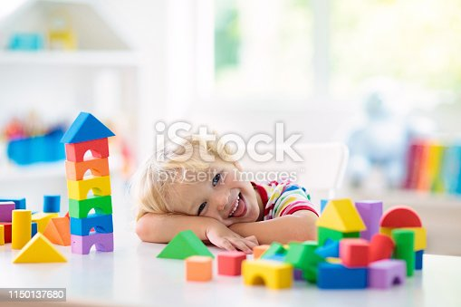 istock Kids toys. Child building tower of toy blocks. 1150137680
