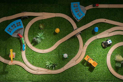 Kids toys frame on yellow background, toy wooden railway and train. Top view. Flat lay.