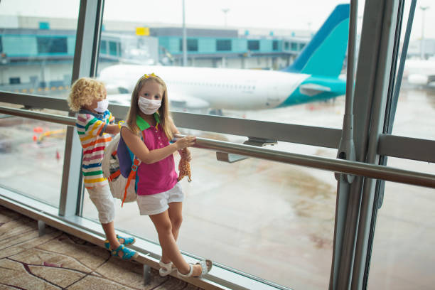 Kids travel and fly. Child at airplane in airport stock photo