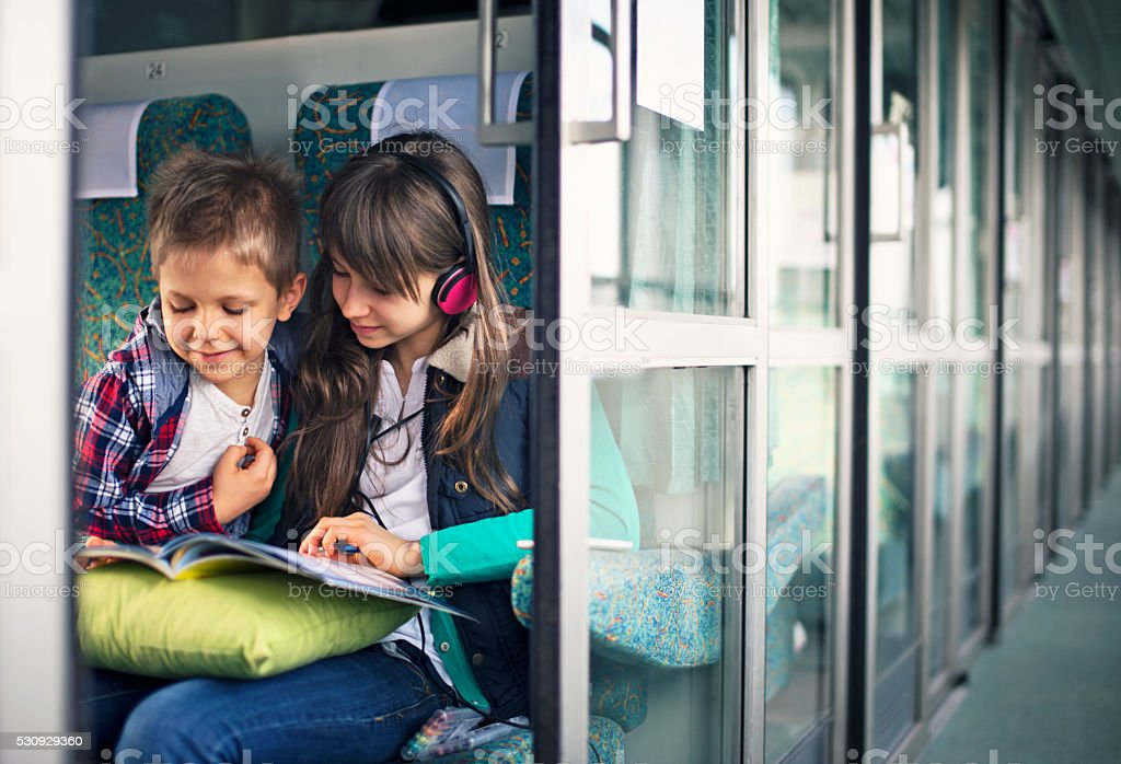 Kids travelling on train reading book and listening to music stock photo