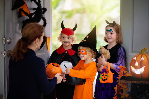 Kids trick or treat. Halloween. Child at door. Kids trick or treat on Halloween night. Child and mother at decorated house door. Boy and girl in witch and vampire costume and hat with candy bucket and pumpkin lantern. Woman with sweets. trick or treat stock pictures, royalty-free photos & images
