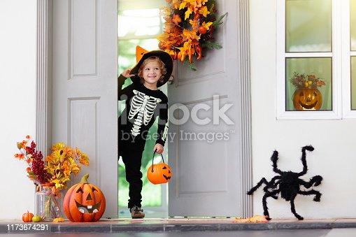istock Kids trick or treat. Halloween. Child at door. 1173674291