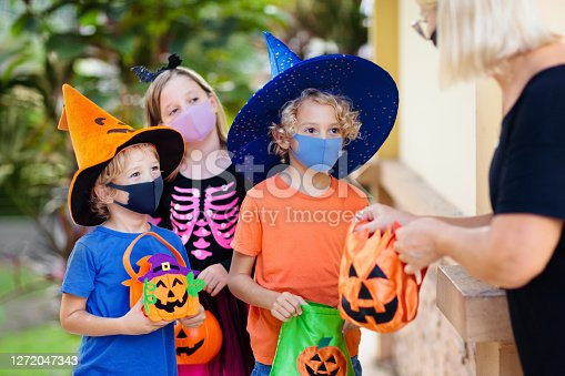Kids trick or treat in Halloween costume and face mask. Children in dress up with candy bucket in coronavirus pandemic. Little boy and girl trick or treating with pumpkin lantern. Autumn holiday fun.