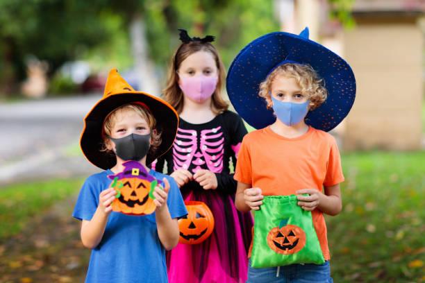 los niños engañan o tratan. halloween con máscara facial. - halloween covid fotografías e imágenes de stock