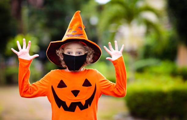 Kids trick or treat. Halloween in face mask. Kids trick or treat in Halloween costume and face mask. Children in dress up with candy bucket in coronavirus pandemic. Little boy and girl trick or treating with pumpkin lantern. Autumn holiday fun. halloween covid stock pictures, royalty-free photos & images