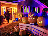 Kids Trick or treating on Halloween night in suburban Californian house decorated with jack o' lantern pumpkins. Photographed in San Jose, California with the p20pro mobile phone.
