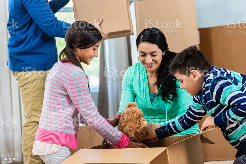 Kids unpack teddy bear from box stock photo