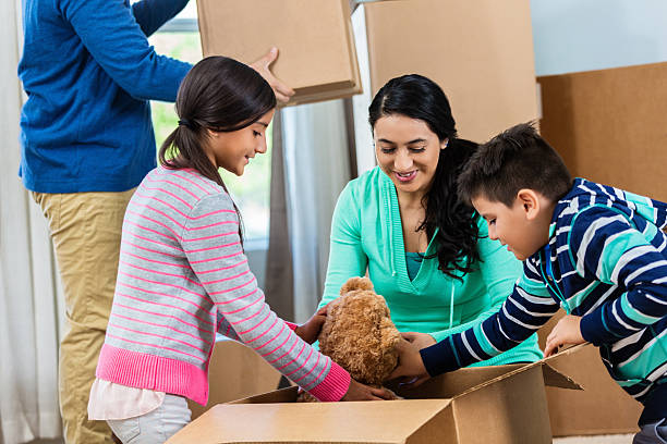 kids unpack teddy bear from box - happy mom packing some toys stock photos and pictures