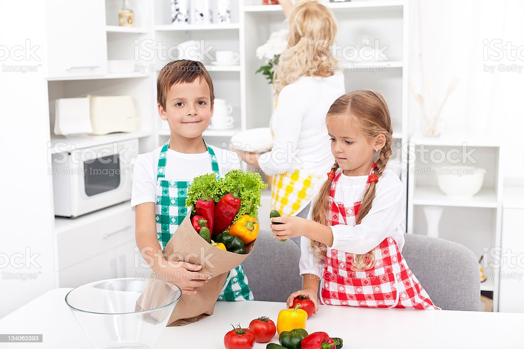 Kids unpacking groceries in the kitchen royalty-free stock photo