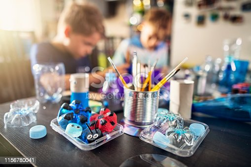 Two boys making fun making fun stuff from garbage at home. They are using plastic bottles, cans to create toys and useful stuff. Nikon D850