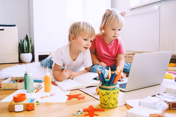 Kids using computer online technology to art creative, drawing or making crafts. Preschool children distance online education. stock photo