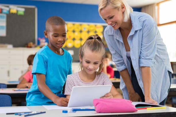 Crianças usando tablet digital em sala de aula - foto de acervo