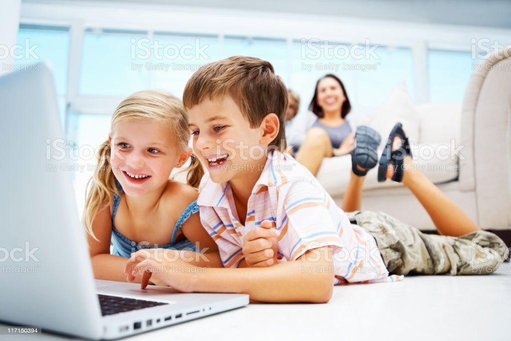 Kids using laptop on floor with parents in the background royalty-free stock photo
