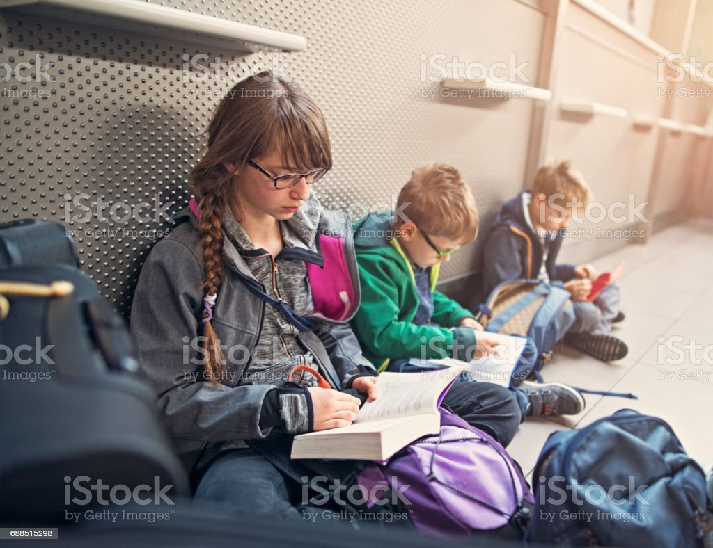 Kids waiting at the airport and reading books stock photo