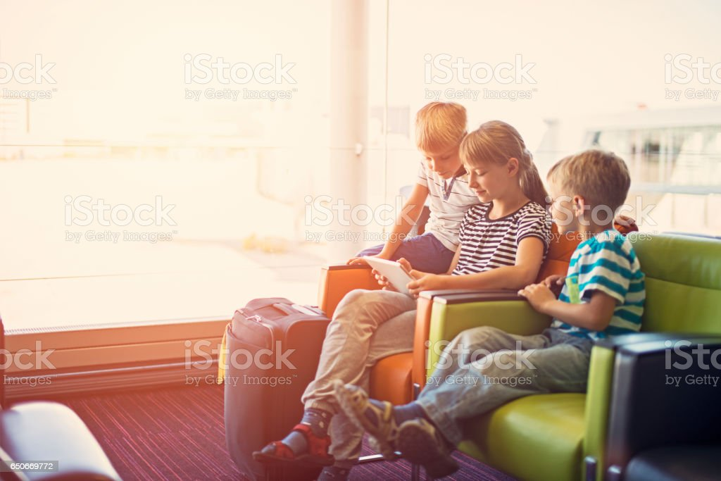 Kids waiting at the Paris airport playing with tablet stock photo