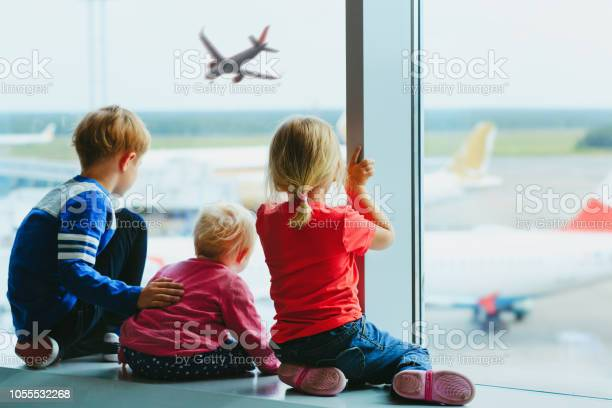 kids waiting for plane in airport, family travel