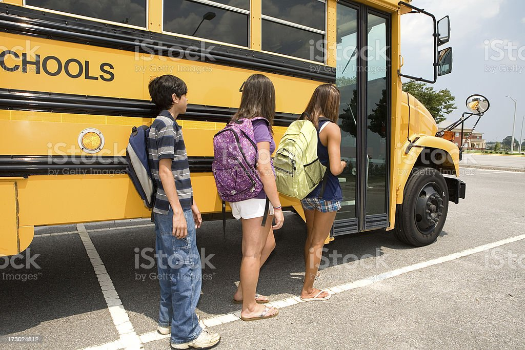 3 kids waiting to get on the bus stock photo