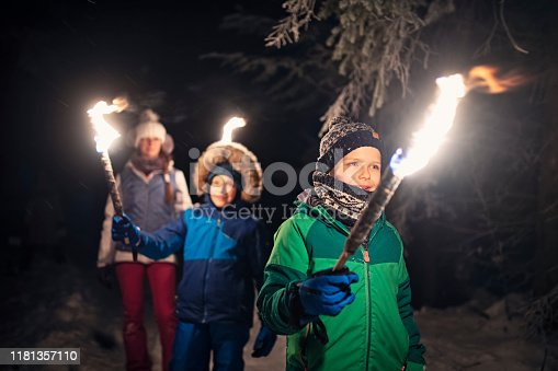 Three kids hiking in beautiful winter forest at night. Kids are holding flaming torches. Nikon D850