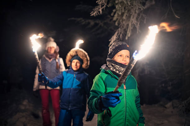 Kids walking in winter forest with torches Three kids hiking in beautiful winter forest at night. Kids are holding flaming torches. Nikon D850 flaming torch stock pictures, royalty-free photos & images