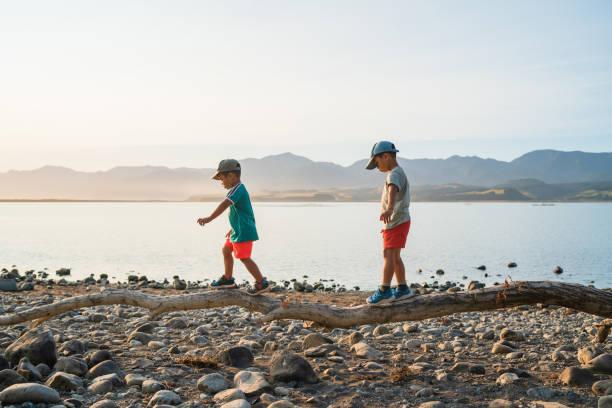 Kids walking on log trying to balance. stock photo