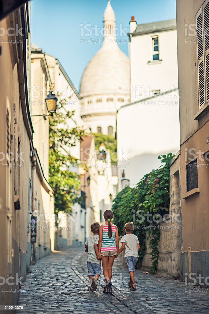 Kids walking towards Sacre Coeur in beautiful street of Montmartre stock photo