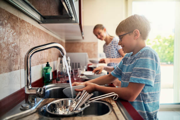 Kids washing up dishes after lunch Three kids washing up dishes in kitchen. The boys and a girl are working together to help their parents. Nikon D850 chores stock pictures, royalty-free photos & images