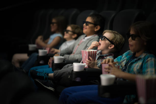 Kids watching a movie at the cinema wearing 3D glasses Happy group of kids watching a movie at the cinema wearing 3D glasses and eating popcorn while smiling 3 d glasses stock pictures, royalty-free photos & images