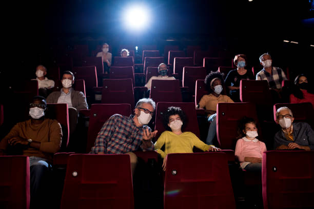 Kids watching a movie with grandparents and wearing face masks at the cinema stock photo