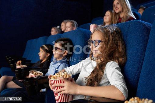 istock Kids watching movie in cinema, holding popcorn buckets. 1147577609