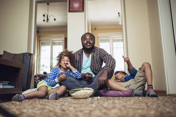 Kids watching movie with their father at home. Family moments. Kids watching movie with their father at home. They are sitting on the living room floor and eating popcorn stay at home father stock pictures, royalty-free photos & images