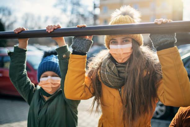 Kinder, die Antiviren-Masken tragen, spielen draußen – Foto