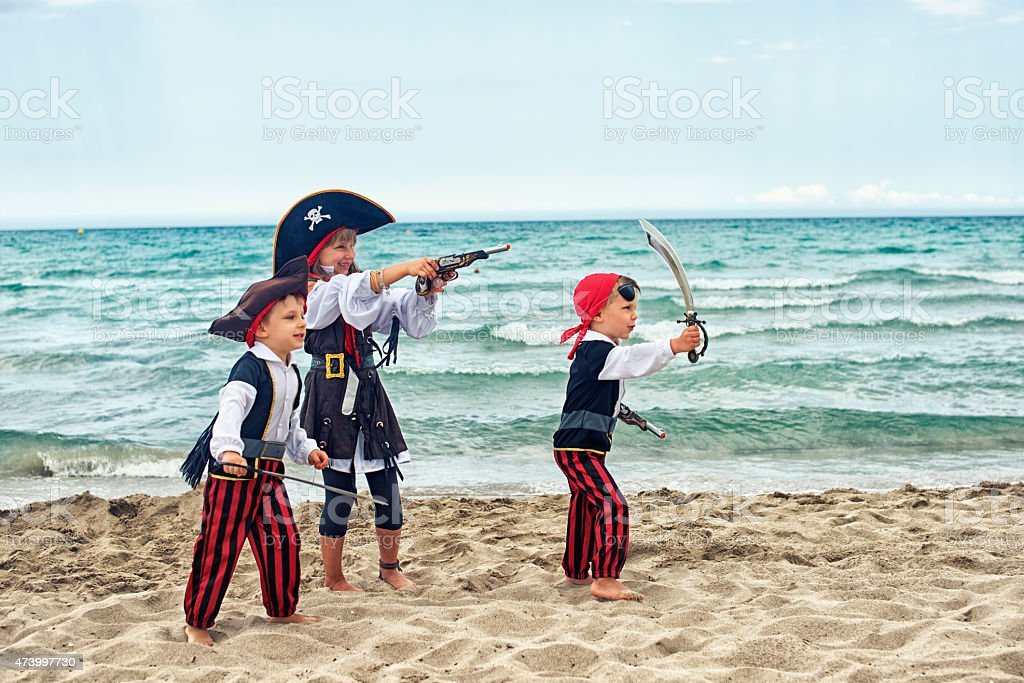 Kids wearing pirate costumes playing on the beach. stock photo